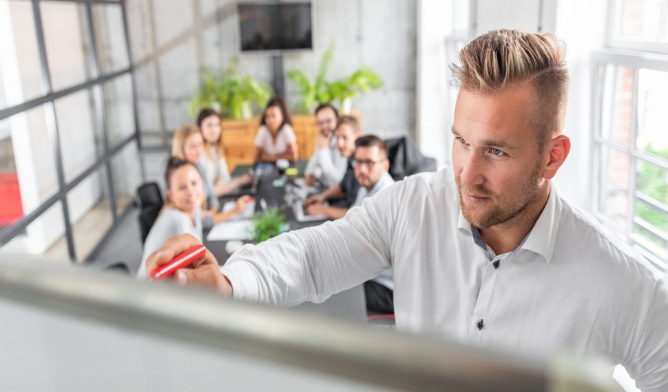 Business coach. Team leader teaches employees at a business meeting in a conference room.